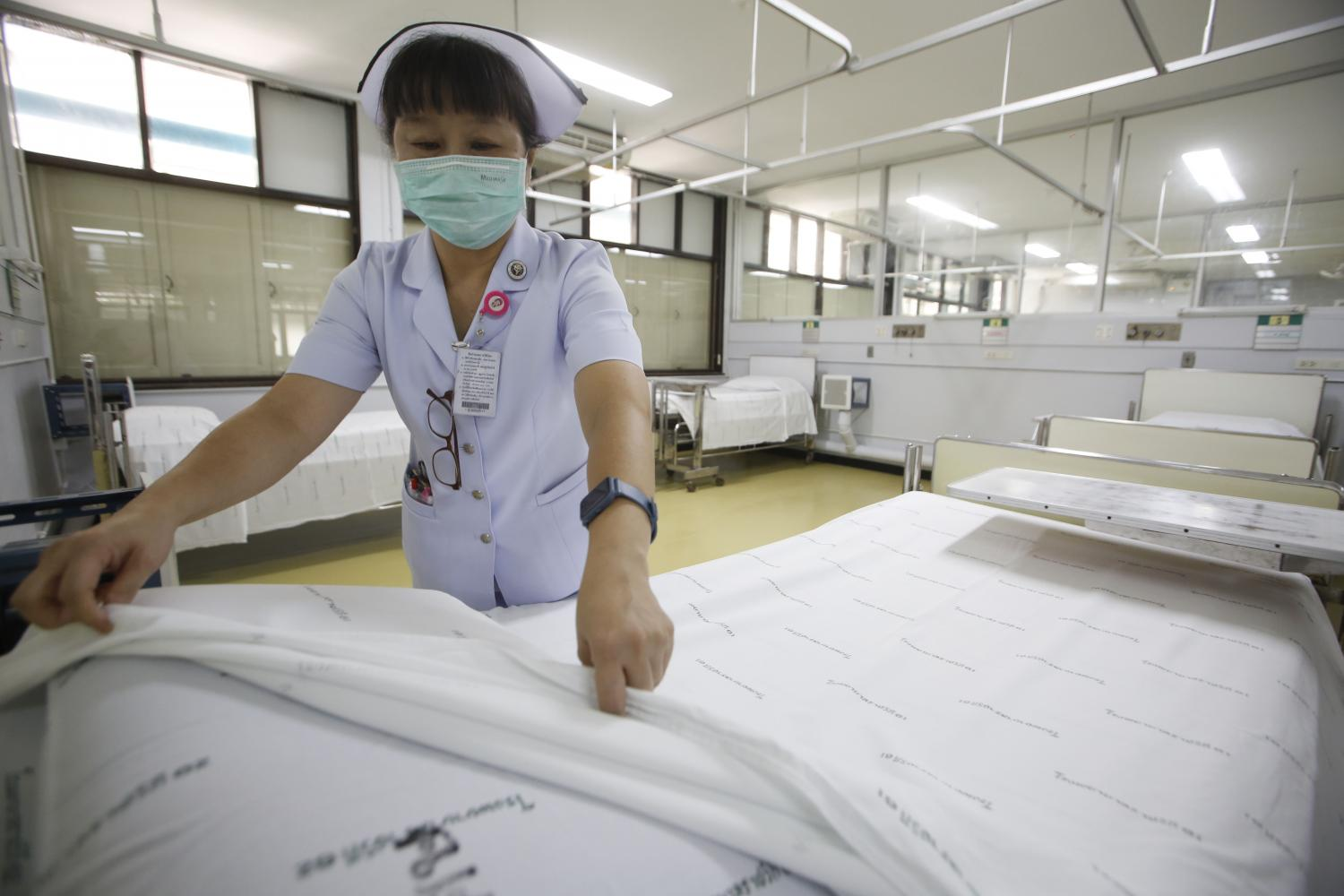 A nurse straightens bed sheets to accommodate Covid-19 patients at Rajavithi Hospital. The coronavirus pandemic has led to a run on insurance to manage unexpected risk.Pornprom Satrabhaya