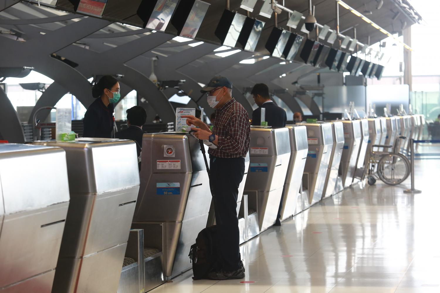 A passenger at a check-in counter Suvarnabhumi airport. The arrival of 26.6 million tourists may be the best-case scenario this year. (Photo by Somchai Poomlard)