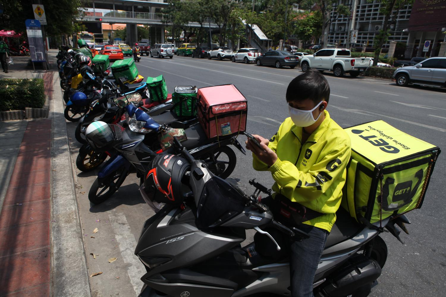 A delivery man calls his customer as he waits to pick up his order in the Siam Square area. Arnun Chonmahatrakool