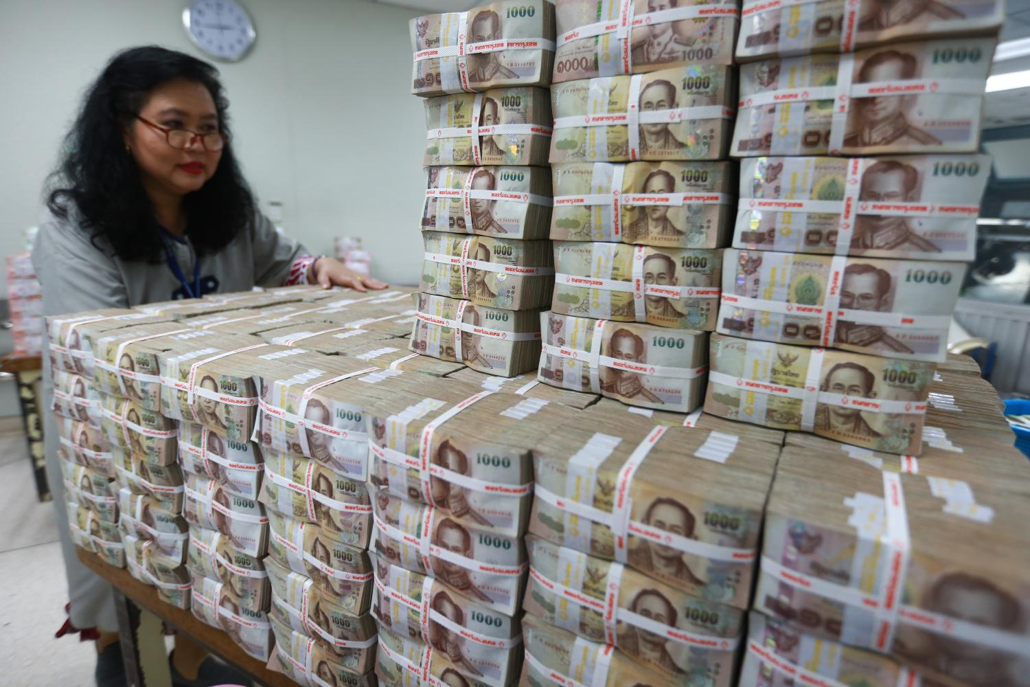 A Bangkok Bank employee gathers stacks of thousand-baht banknotes. A senior BoT official said banks have a sufficient capital buffer in the event of higher past-due payments and debt restructuring. (Photo by Somchai Poomlard)