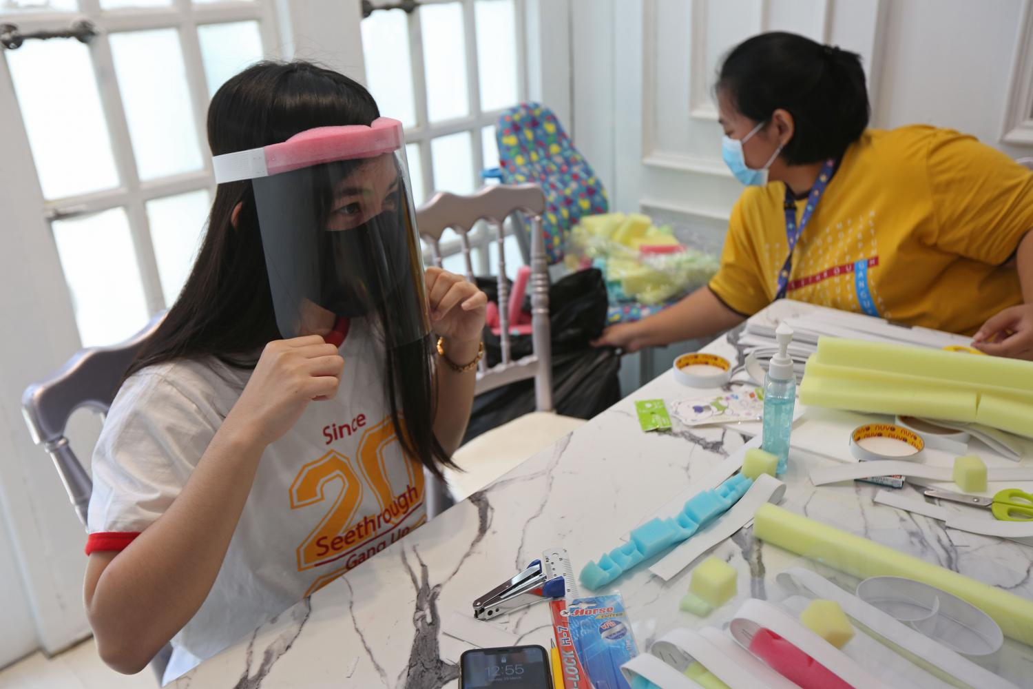 SAFETY GLASS: A young woman tests one of the face shields she produces at her home in Lat Phrao area of Bangkok. The shields will be donated to medical personnel at hospitals treating Covid-19 patients. photo:Varuth Hirunyatheb