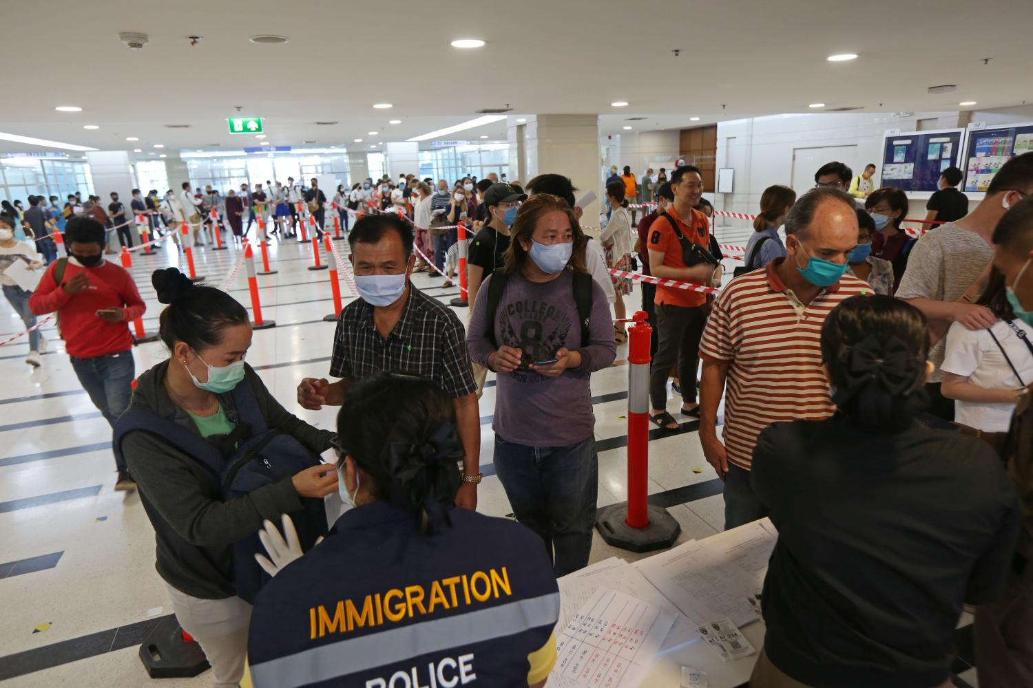 Foreigners queue in long lines at the Immigration Bureau's office in Chaeng Watthana. (Photo by Varuth Hirunyatheb)