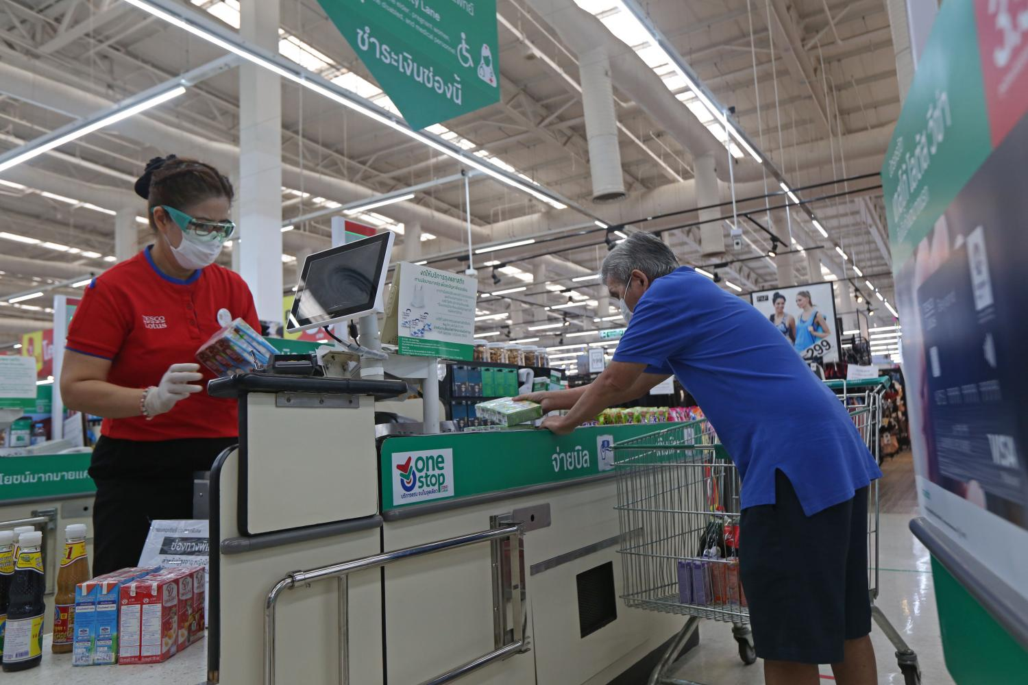A cashier serves a customer at a hypermarket in Bangkok. Cashiers are under threat as it is an occupation that can be done by artificial intelligence and digital technologies.  (Photo by Varuth Hirunyatheb)