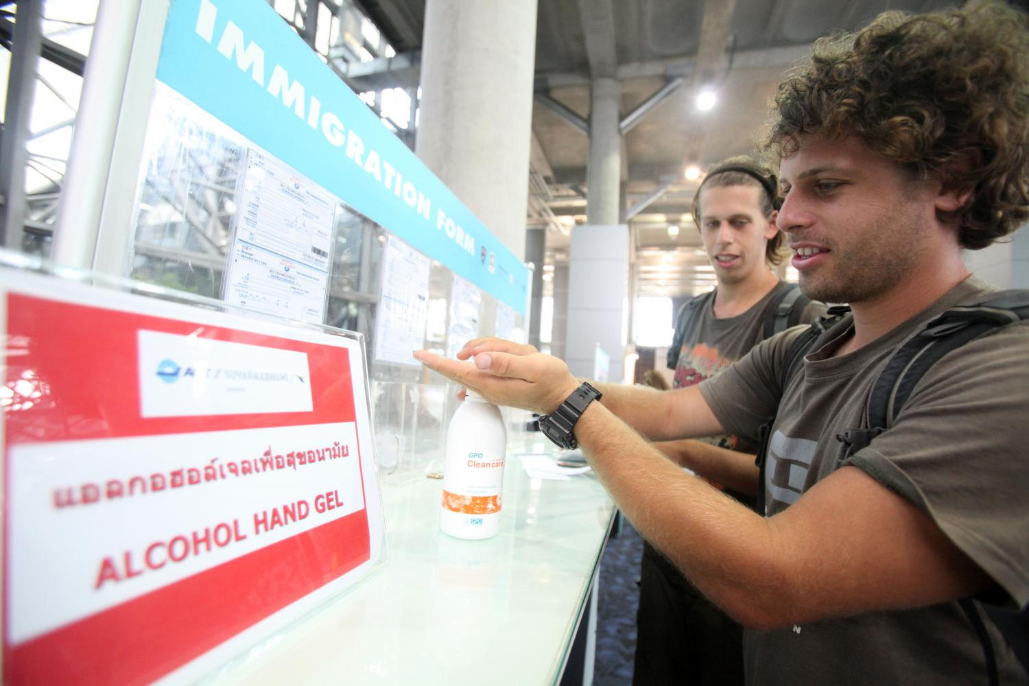 Tourists use alcohol-based hand sanitiser at Suvarnabhumi airport as demand for alcohol disinfectant has surged since the outbreak. (Photo by Taweechai Tawatpakorn)