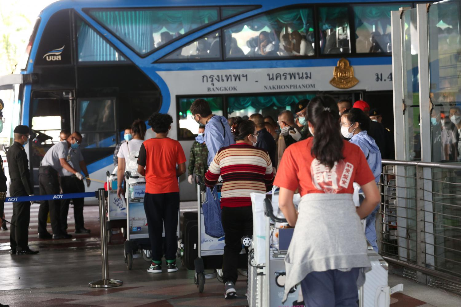 Twenty-six returnees from Japan go straight to a bus which will take them to a hotel in Bangkok for a 14-day quarantine. A total of 32 arrived from Haneda airport, but six did not pass screening and were sent to hospital. Varuth Hirunyatheb
