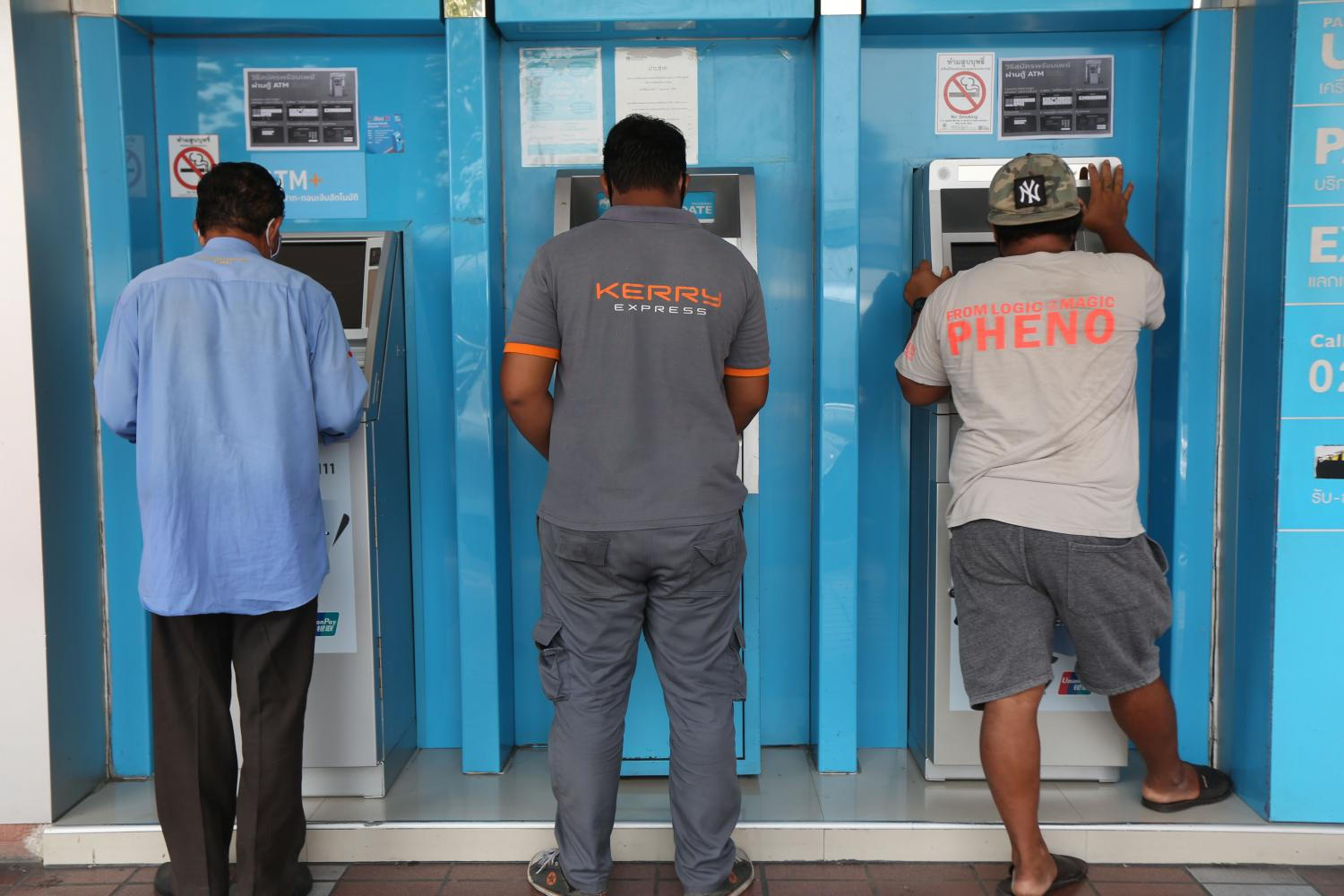 City people withdraw 5,000-baht cash handouts from ATM machines. The handouts are from the government as part of a relief package to alleviate hardship as a result of tough measures to curb the Covid-19 outbreak, which has caused an economic downturn.(Photo by Varuth Hirunyatheb)