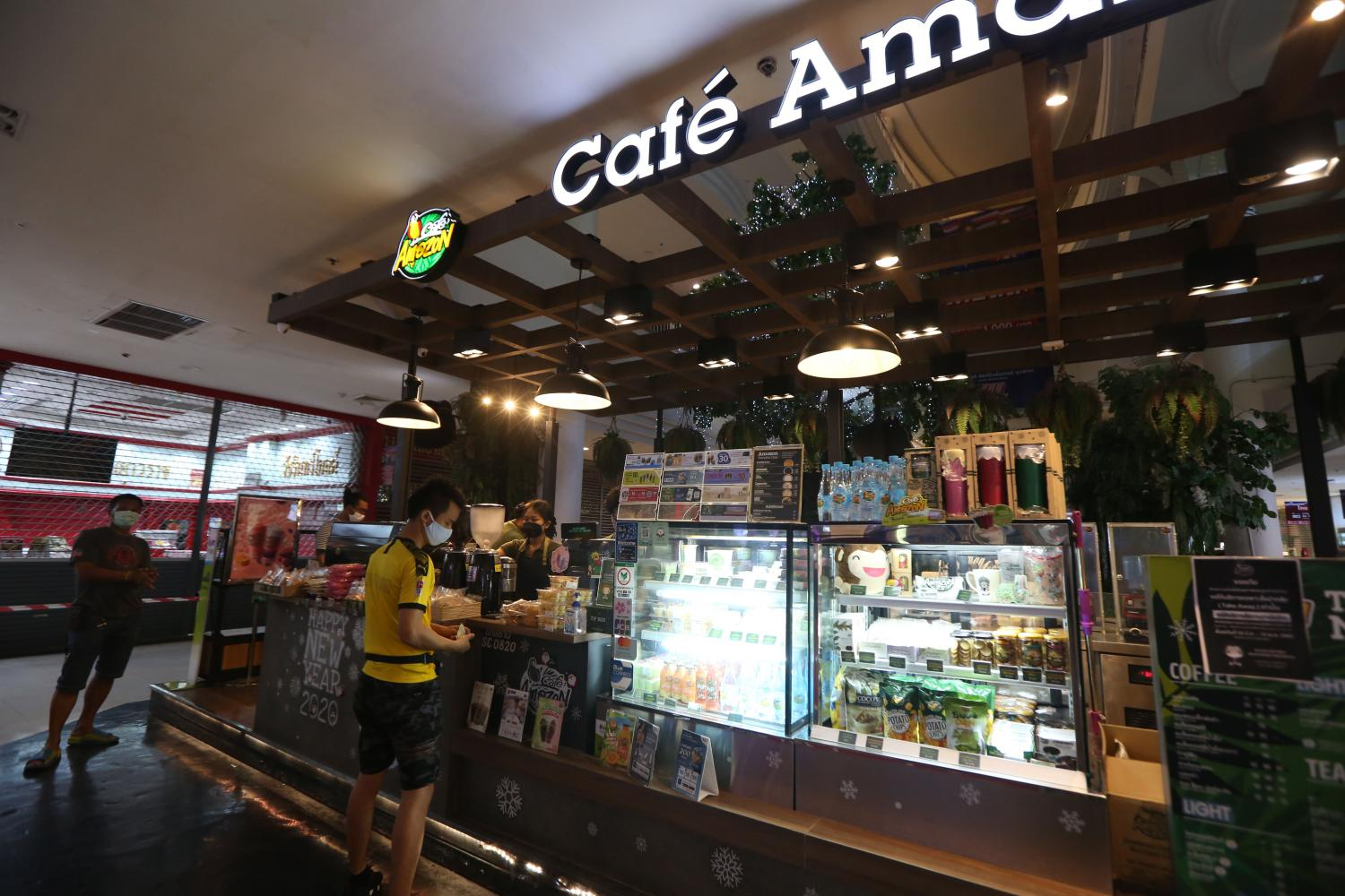 A visitor wears a face mask at Cafe Amazon. The coffee shop chain is owned by state energy firm PTT, which has seen sales plummet amid the coronavirus outbreak.(Photo by Varuth Hirunyatheb)