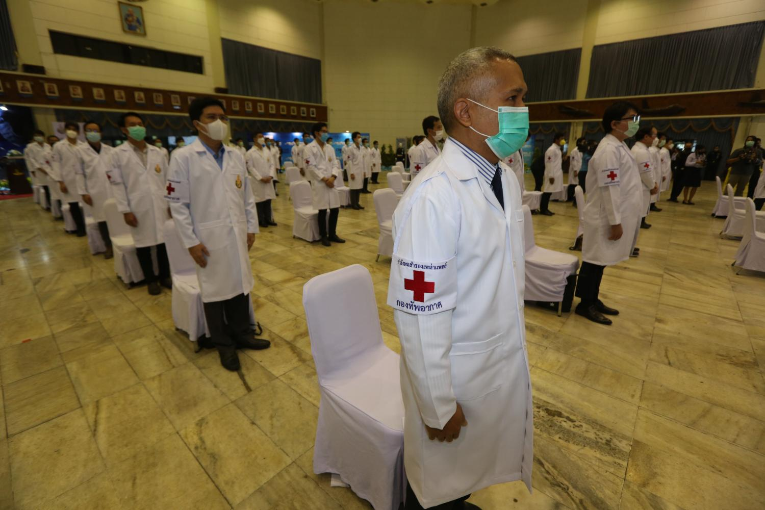 Fifty former military doctors rise as they reenlist in the Royal Thai Air Force to help fight the Covid-19 pandemic amid a rising number of cases. (Photo by Varuth Hirunyatheb)