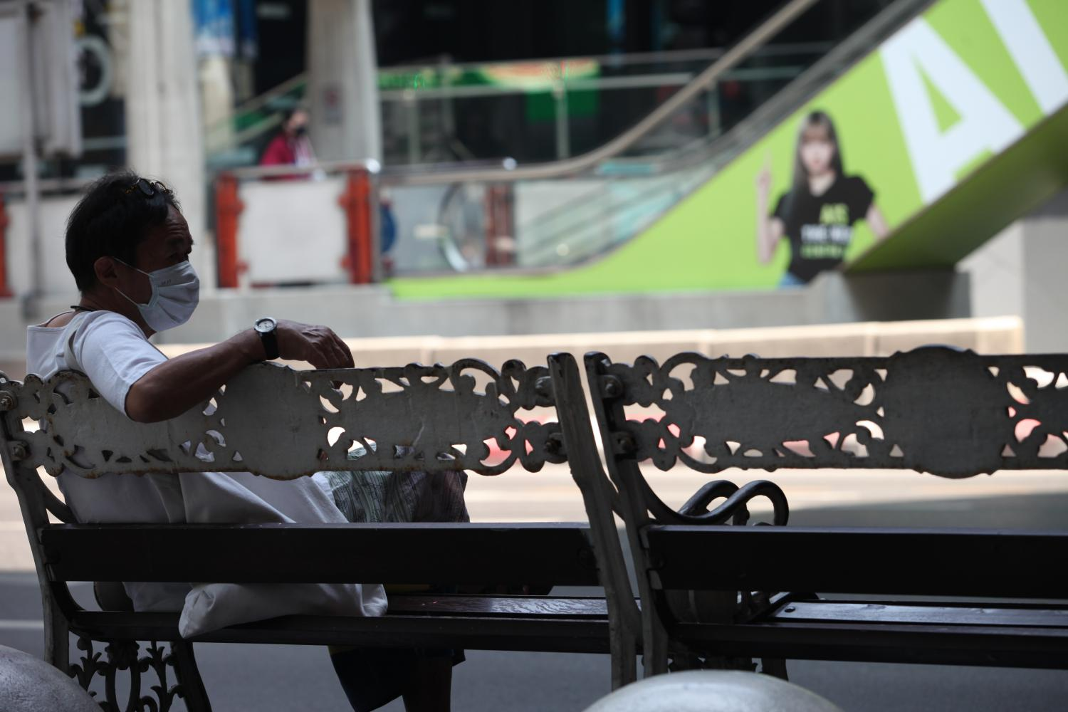 NOTHING TO SEE HERE: A man sits alone on a bench in Siam Square, a popular shopping district in Bangkok which has become almost empty since lockdown measures were ramped up to prevent the spread of Covid-19.