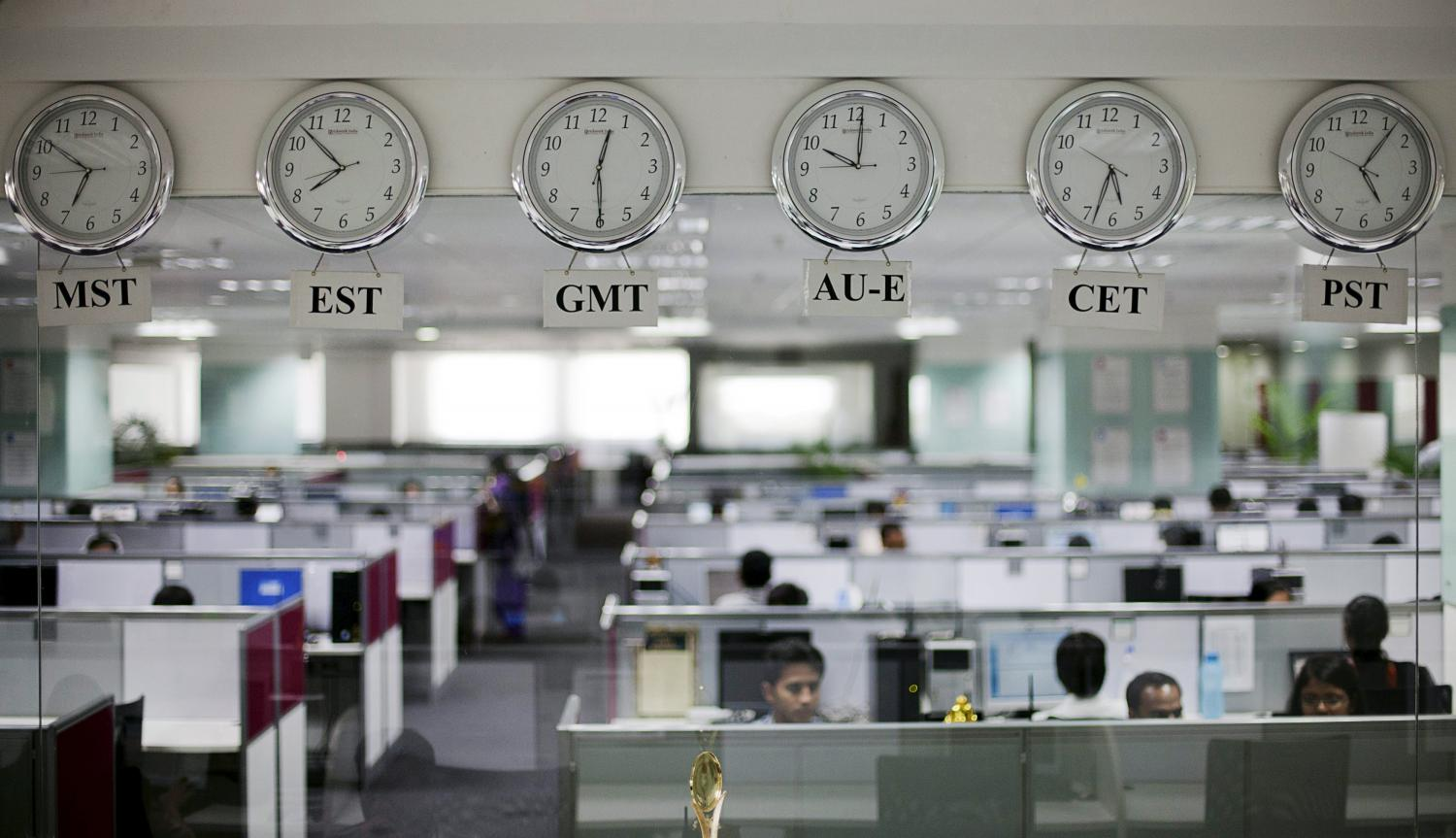 Workers are pictured beneath clocks displaying time zones in various parts of the world at an outsourcing centre in Bangalore in this file photo. (Reuters photo)