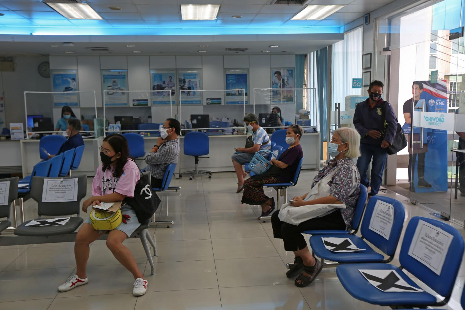 Customers maintain social distance while waiting to receive cash handouts at Krungthai Bank. The Finance Ministry says an additional 400 billion baht is available for the scheme if needed. (Photo by Varuth Hirunyatheb)
