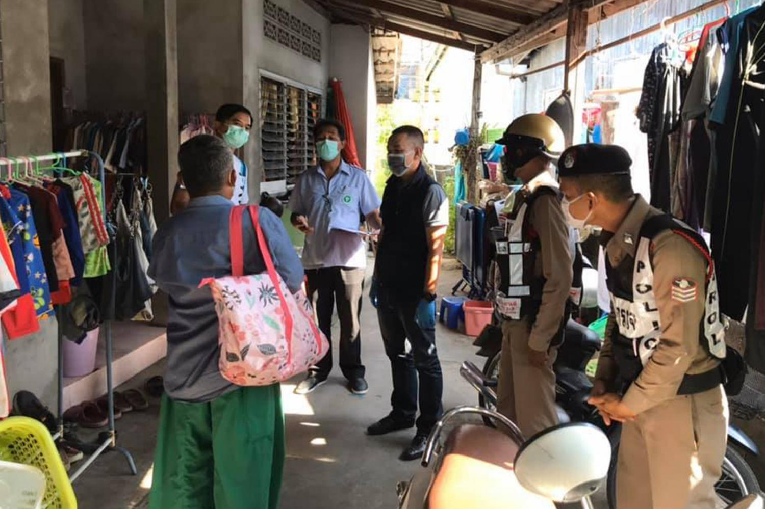 Health officials and police talk to residents at Ban Bang Thao village in Thalang district of Phuket to find people suspected of contracting Covid-19 or those who have come into contact with them.