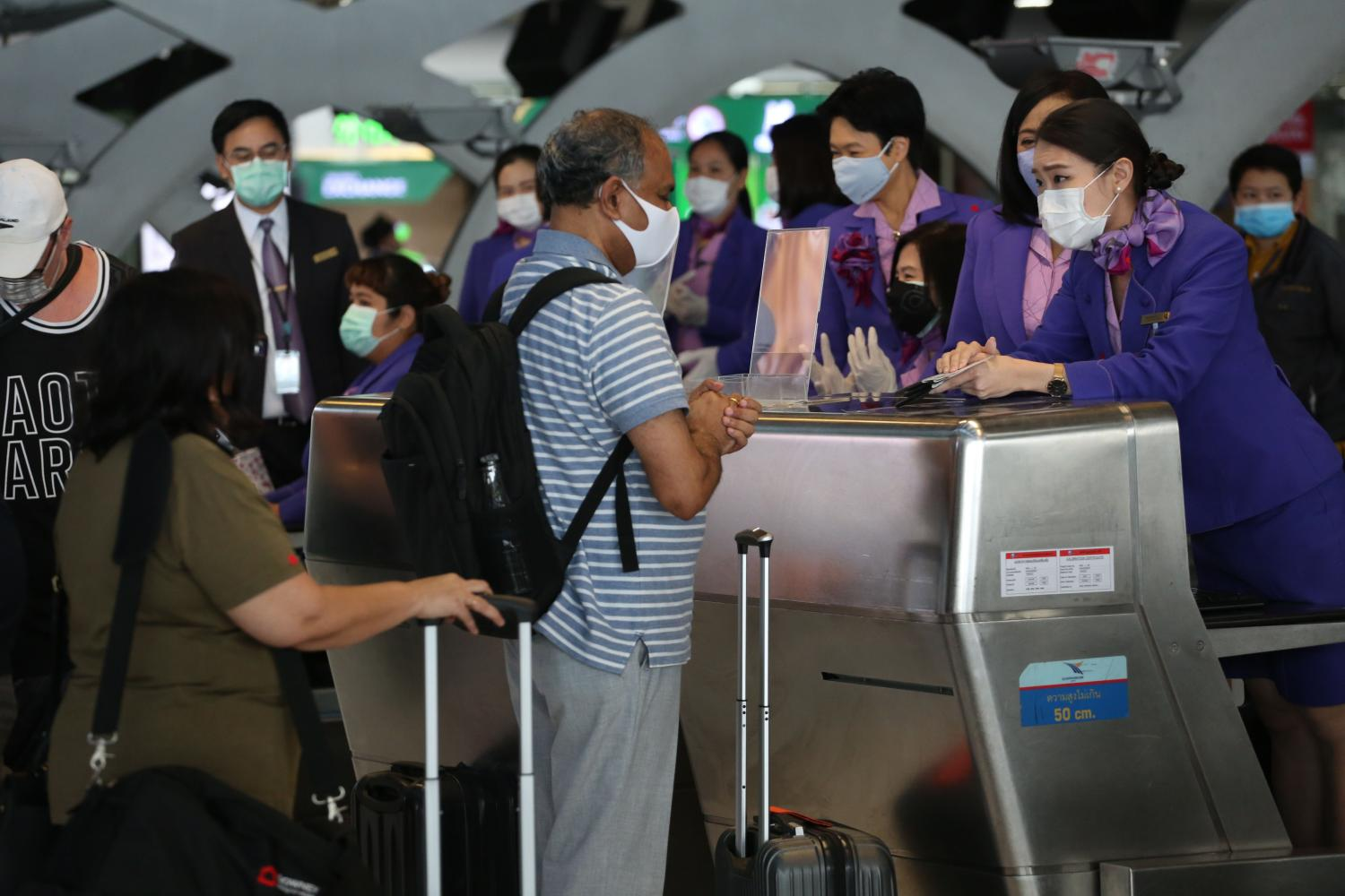 Passengers on Sunday check in at a THAI counter at Suvarnabhumi Airport to board a chartered flight from Bangkok to Auckland in New Zealand. (Bangkok Post photo)