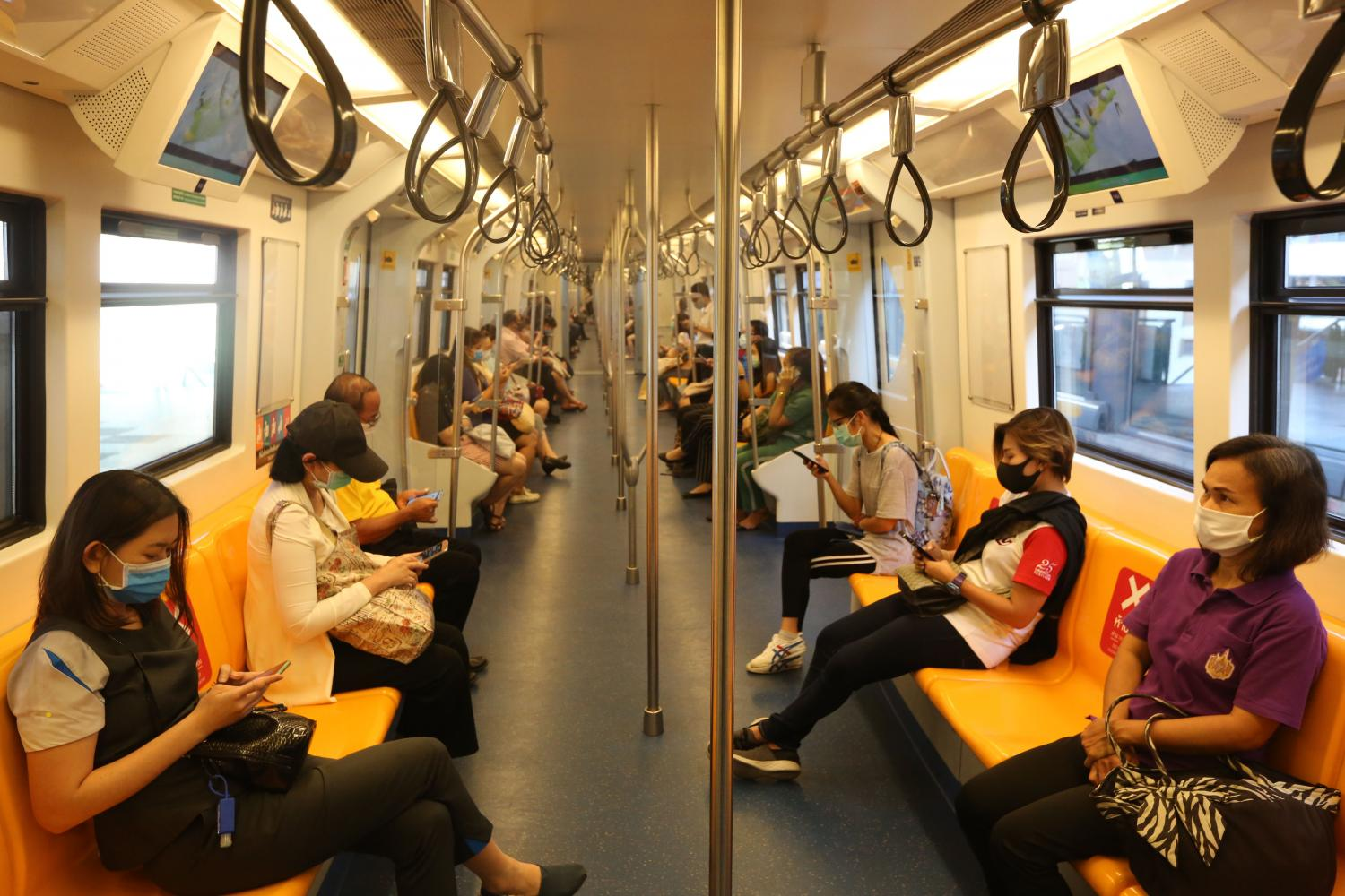 below Skytrain commuters use social distancing to prevent the spread of contagious disease.Wichan Charoenkiatpakul