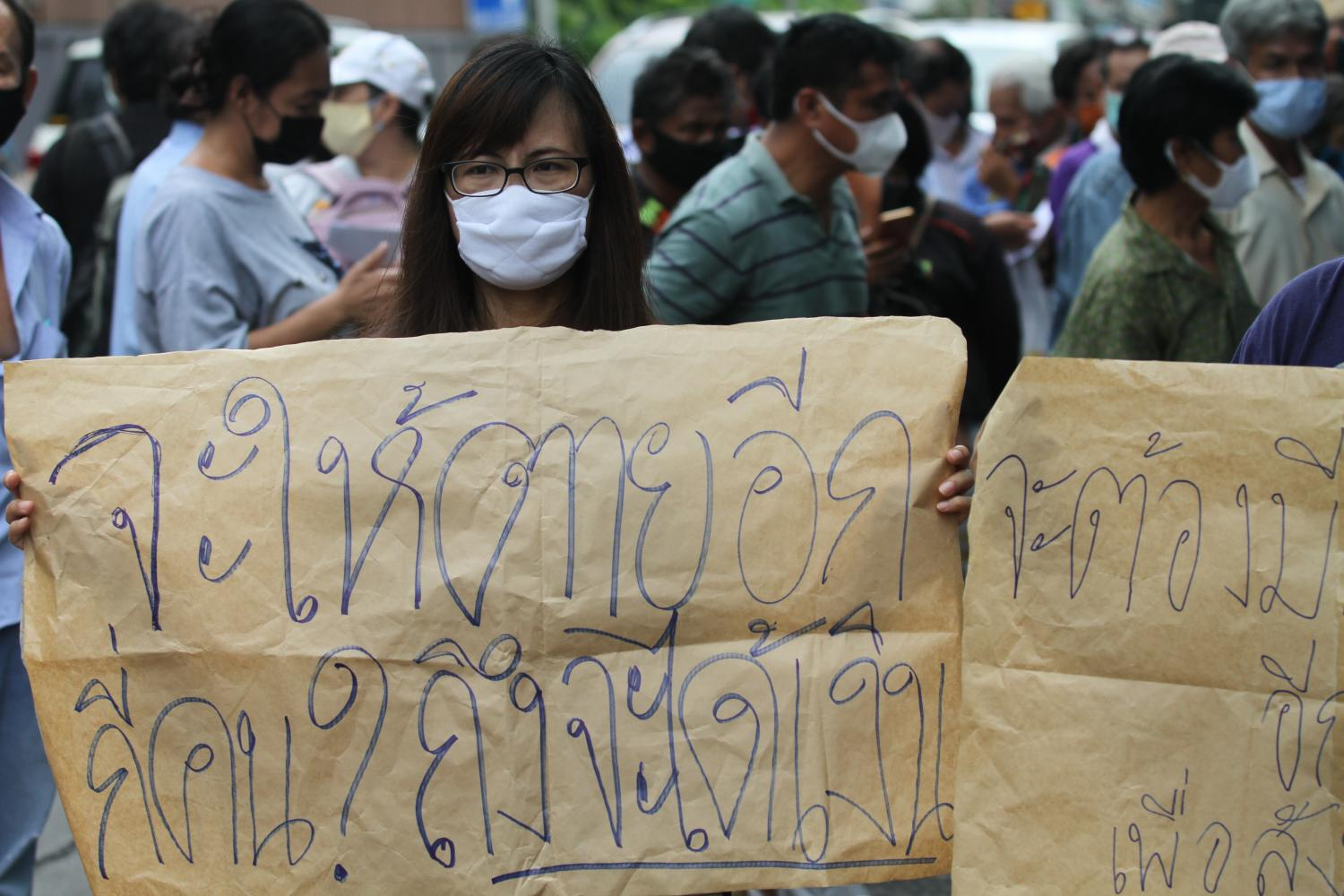 People who missed out on the government's 5,000-baht aid money turn up at the Finance Ministry to lodge complaints this week. One woman holds a placard which reads 'How many will have to die before the government extends help?'(Photo by Nutthawat Wicheanbut)