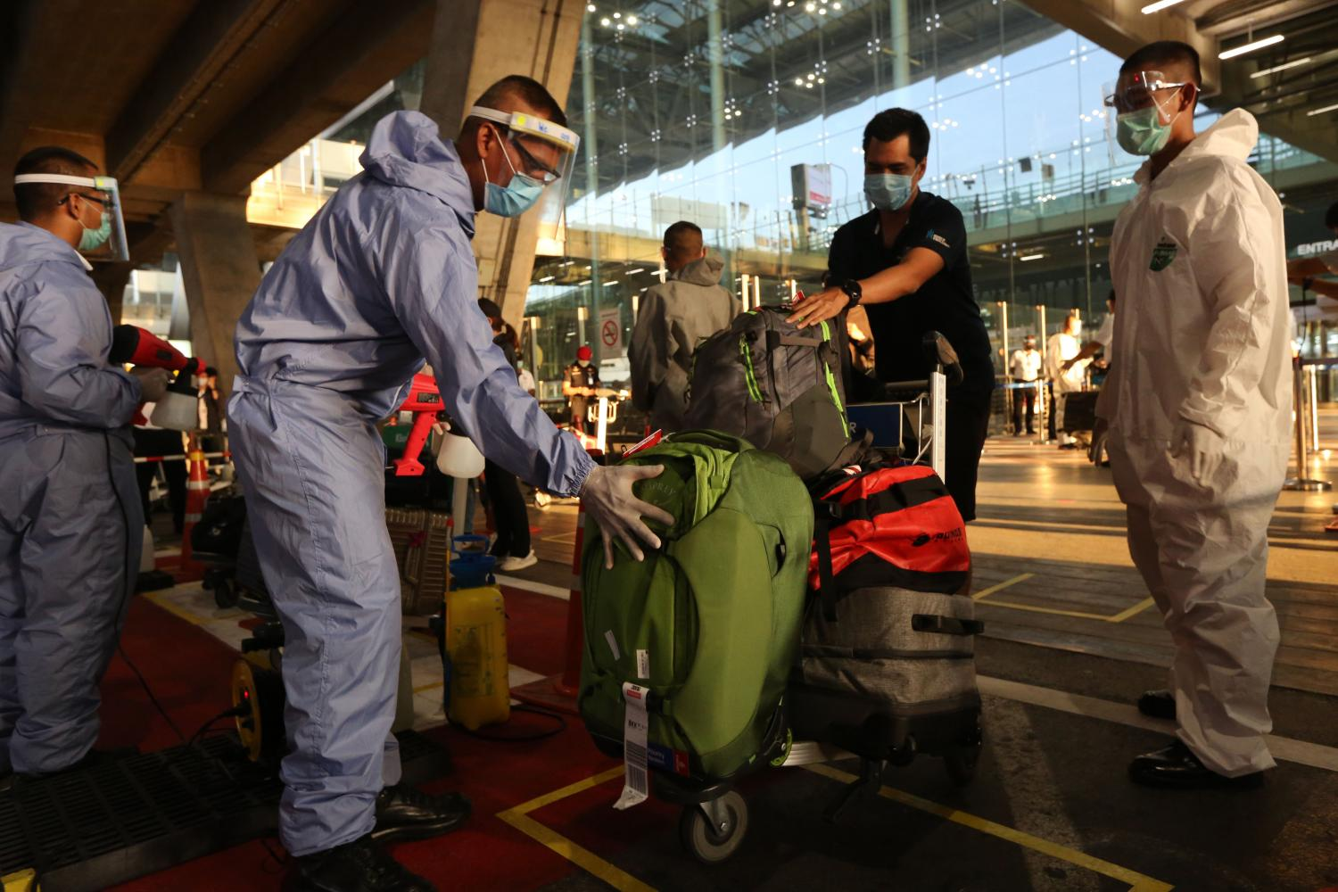 Staff disinfect the luggage of Thai returnees from the UAE who arrived on Saturday at Suvarnabhumi Airport.