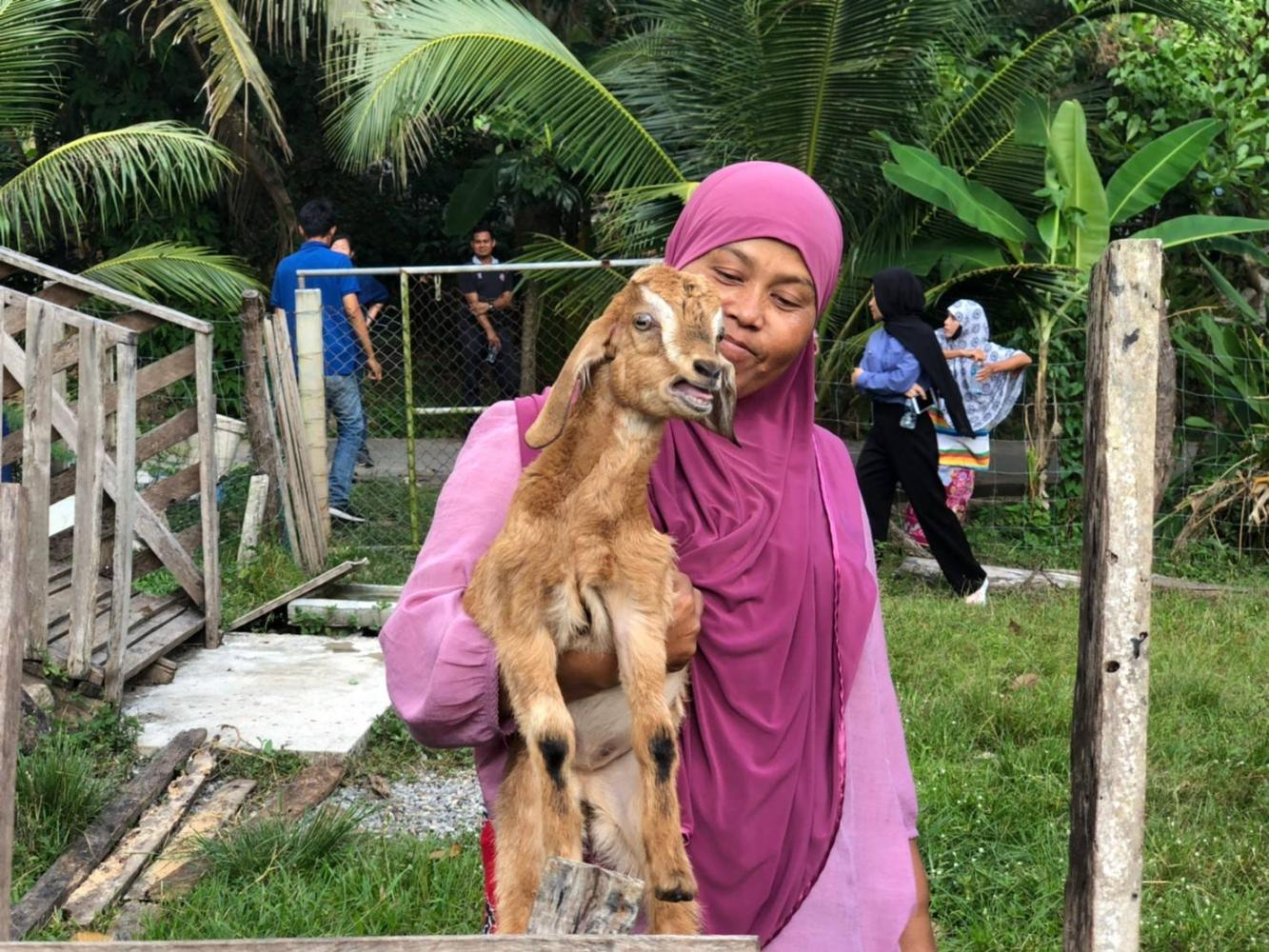 Sunee Chumnopparat holds a goat at a community farming enterprise in Pattani. Modern goat-raising techniques have boosted the quality of life of local Muslims.CHATRUDEE THEPARAT