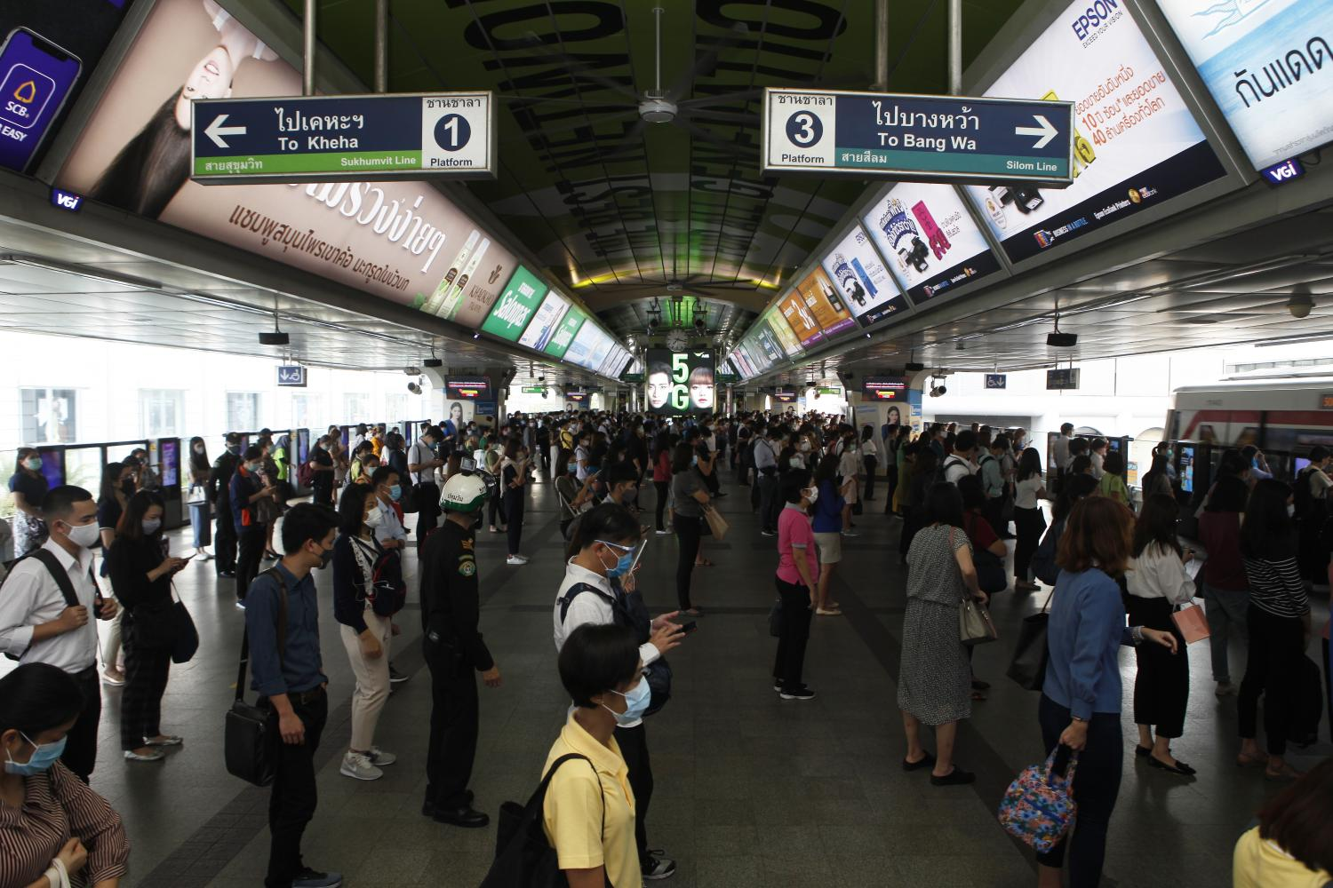 Commuters line up with space between them as they wait to catch a train at the busy Siam Station on Thursday. It was a starkly different scene from Tuesday morning when a BTS breakdown saw commuters packed into trains during rush hour.