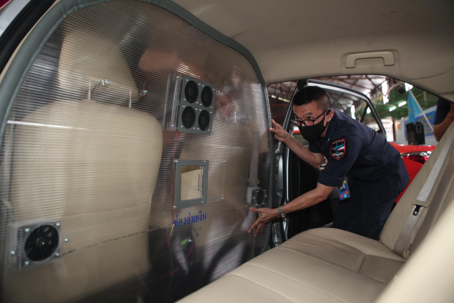 A a special partition designed by the Royal Thai Air Force is installed in a taxi to help prevent transmission of the coronavirus. Known as a 'taxi bulkhead barrier', it can be installed and removed without the need to modify the interior of the vehicle. Apichart Jinakul