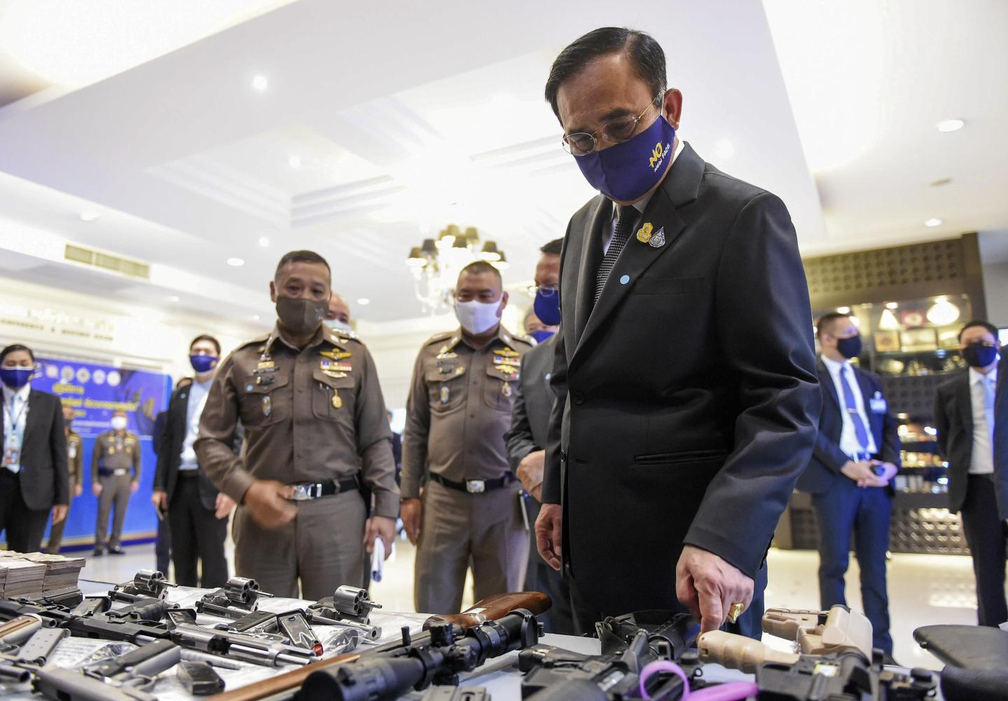 Prime Minister Prayut Chan-o-cha looks at weapons seized in a drugs crackdown during his visit to the Office of the Narcotics Control Board on Din Daeng Road in the capital on Friay.(Government House photo)