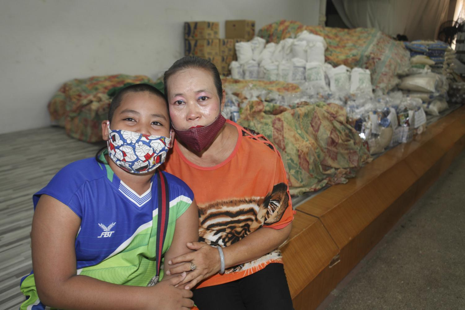 Hard times: Malee Boonmee, 49, and her 10-year-old adopted son Nong Pi have been hit by the lockdown, after Ms Malee lost her job. Her family now has no income and she doesn't know how she will support the education of her two sons when schools reopen in July.