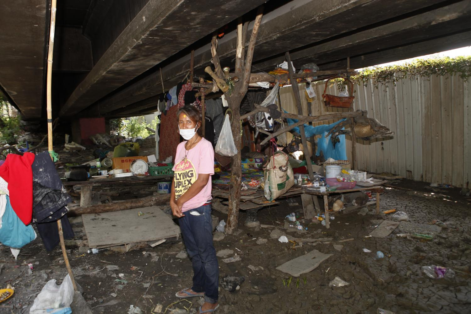 Orathai Srisawas, a deaf woman who lives in a community underneath the Rama IX expressway, stands in front of her shelter. photos by Nutthawat Wichieanbut