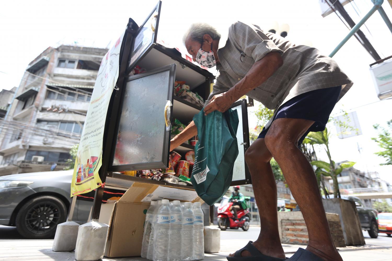 A man selects items he needs from a roadside cupboard on Sukhumvit 71. Wichan Charoenkiatpakul