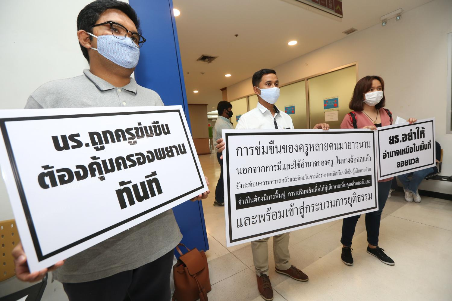 Rights activists hold placards denouncing the alleged gang rape of schoolgirls by teachers and alumni in Mukdahan province.Varuth Hirunyatheb