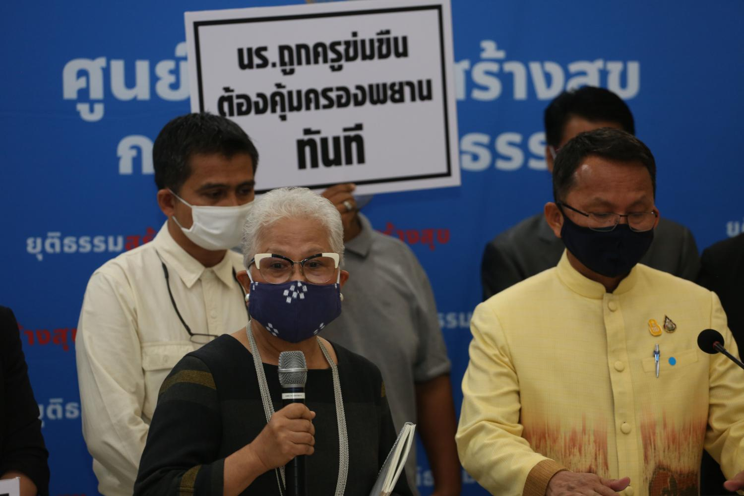 Rights activists led by child protection advocate Thicha Na Nakhon, left, hold placards denouncing the gang rape of schoolgirls by teachers and alumni in Mukdahan province. Varuth Hirunyatheb