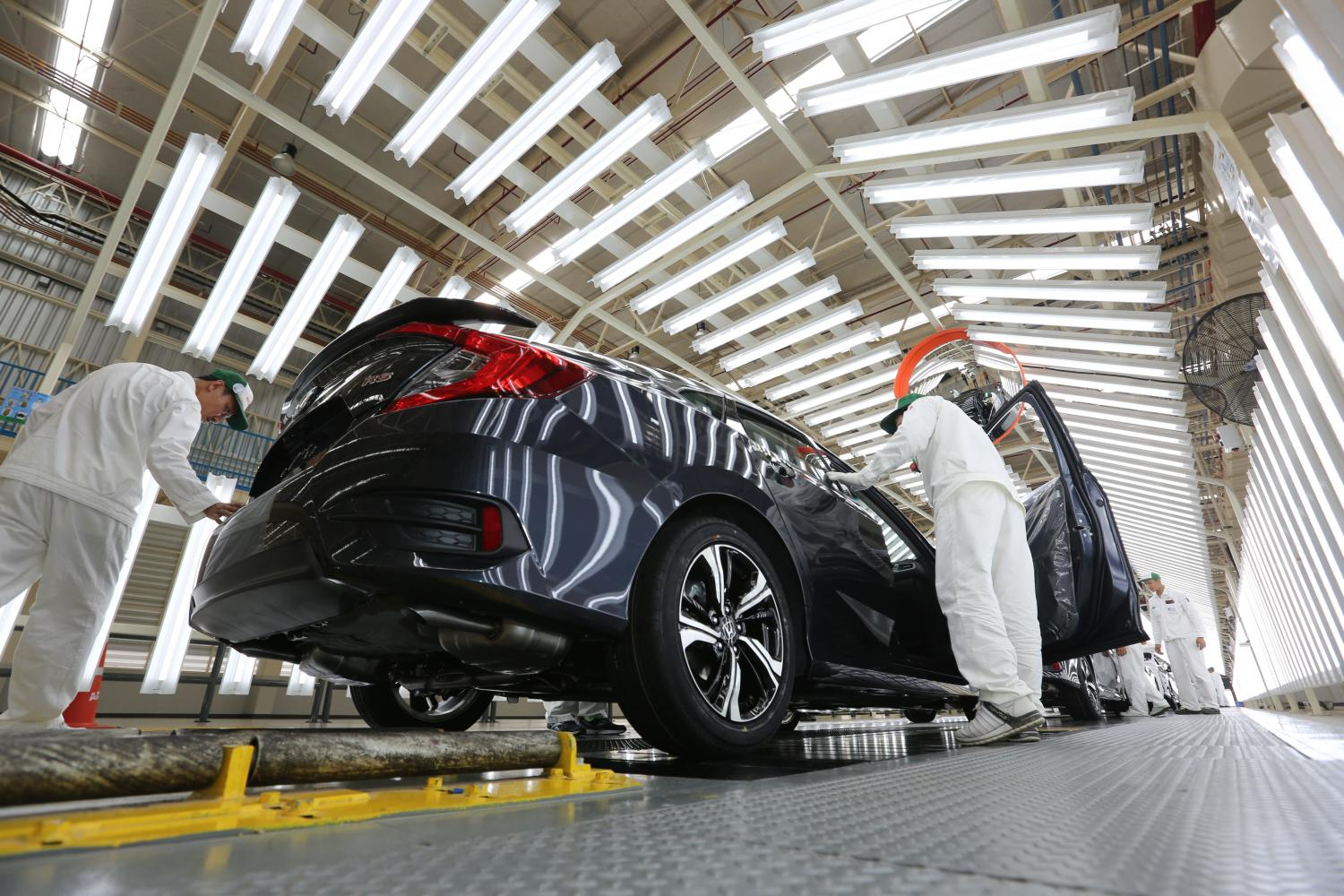 Assembly workers inspect a car at a factory in Prachin Buri. Car production fell 29.4% in the January-April period. Pattanapong Hirunard