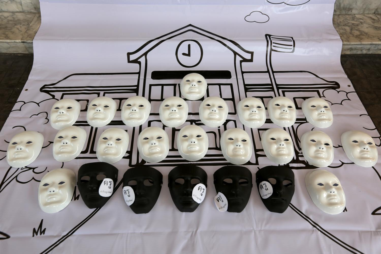 Activists use black masks to represent