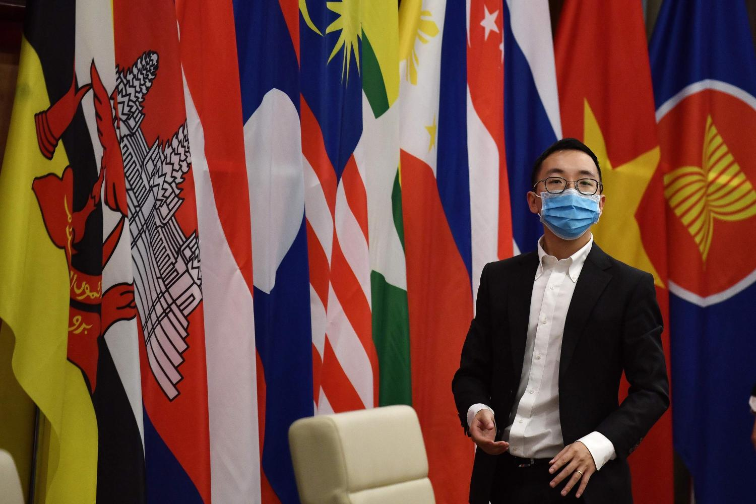 An official wearing a face mask stands next to member flags during the special Association of Southeast Asian Nations Summit on the coronavirus pandemic in Hanoi on April 14, 2020. (AFP photo)