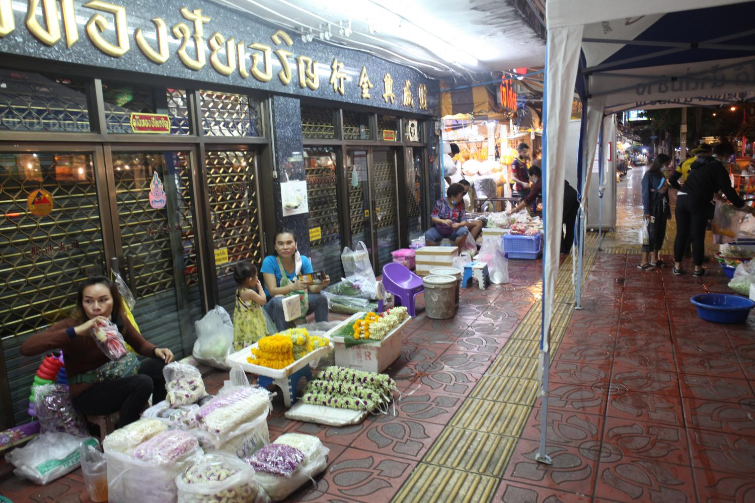In this April 23 file photo, vendors sit idly as the city's flower market is almost empty shortly before curfew time.Arnun Chonmahatrakool