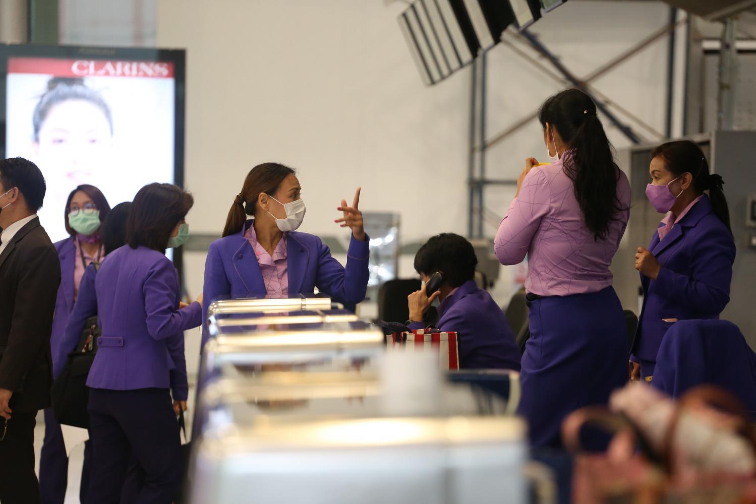Thai Airways International staff at Suvarnabhumi airport prepare for the arrival of a repatriation flight from Italy yesterday.Varuth Hirunyatheb