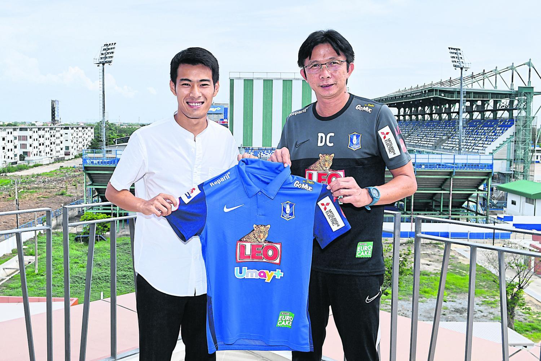 Midfielder Sarach Yooyen (left) poses with BG Pathum coach Dusit Chalermsan.