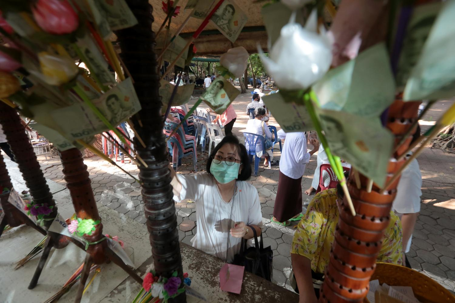 A woman wearing a face mask to protect her from Covid-19 makes merit at a temple earlier this month.(Photo by Chanat Katanyu)