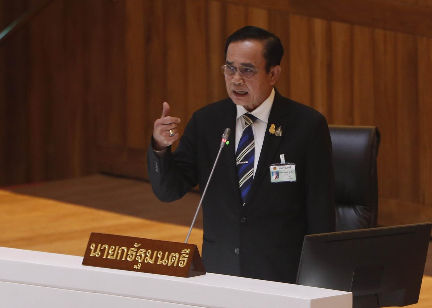 Prime Minister Prayut Chan-o-cha addressing a meeting of the House of Representatives on Wednesday, the first day of a debate on the government's three executive decrees on Covid-19 borrowing. The picture at left shows members of parliament in face masks standing up and keeping sufficient space from one another during the meeting. (Photo by Chanat Katanyu)