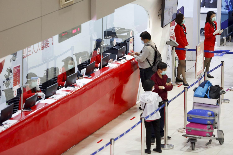 Domestic passengers queue at the Thai AirAsia sales counter at Don Mueang airport. The airline resumed domestic flights on May 1. (Bangkok Post photo)