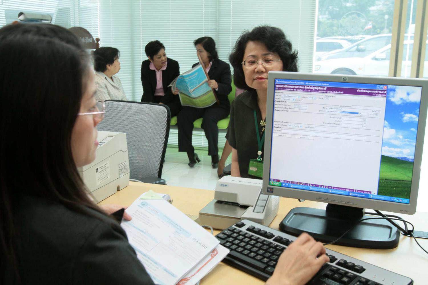 A taxpayer submits personal income tax forms to a revenue official.(Photo by Apichit Jinakul)