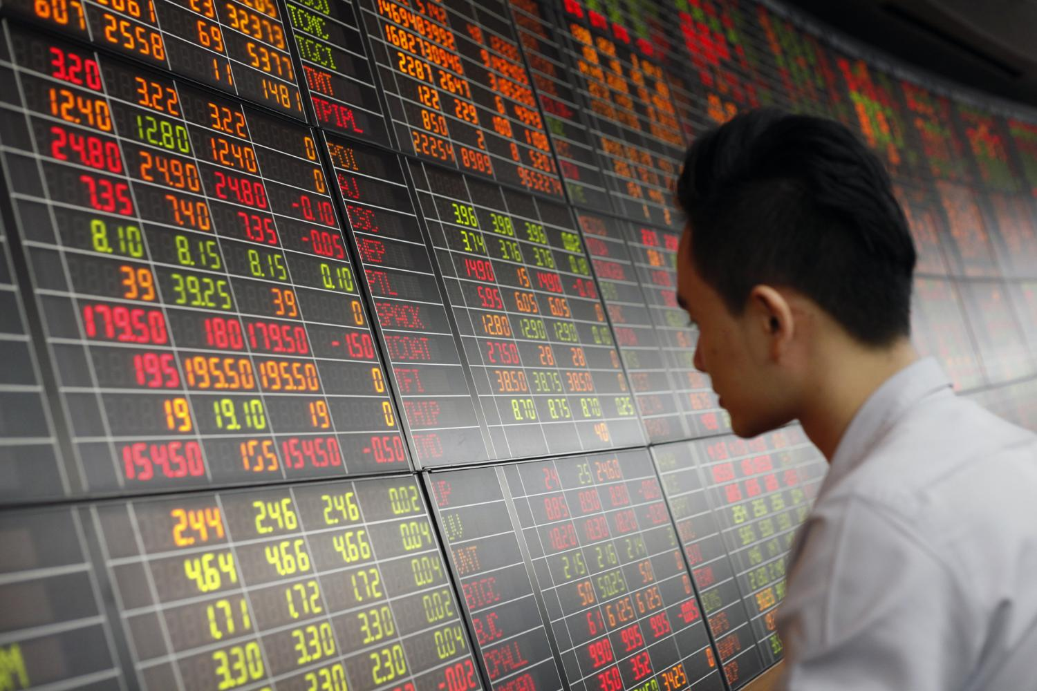 A man looks at an electronic board displaying stock prices at Asia Plus Securities. The SET is expected to fall in the coming months as listed firms have been reeling from the virus impact.(Photo by Pornprom Satrabhaya)