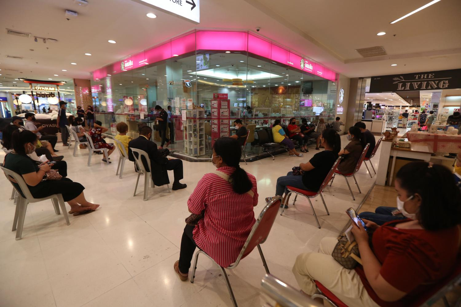 People adhere to social distancing while queuing at a Government Savings Bank branch in a shopping mall. Varuth Hirunyatheb