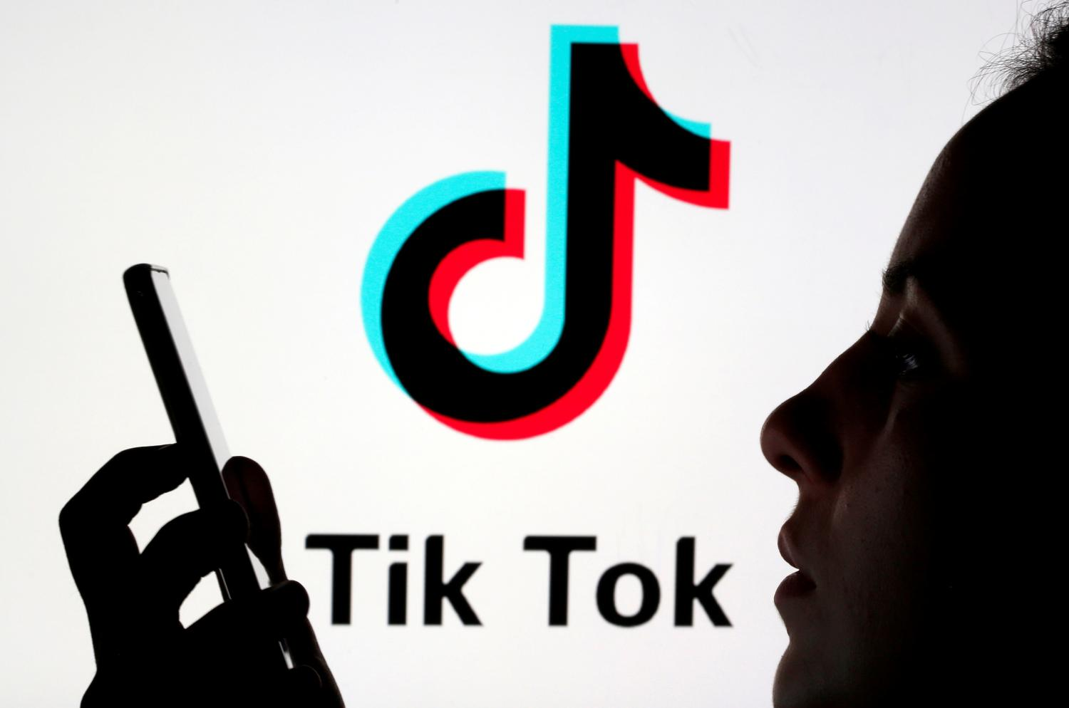 A person holds a smartphone as Tik Tok logo is displayed behind in this picture illustration. (Reuters photo)