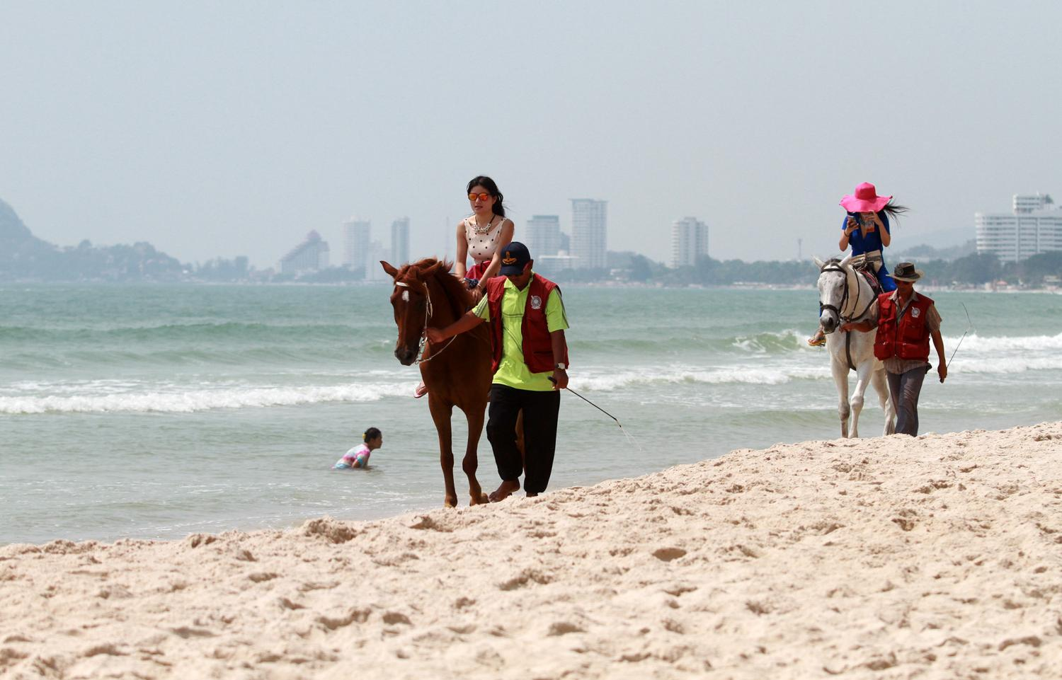 Tourists ride horses at Hua Hin beach. Hotels there recorded higher occupancy in May from locals. Thanarak Khunton