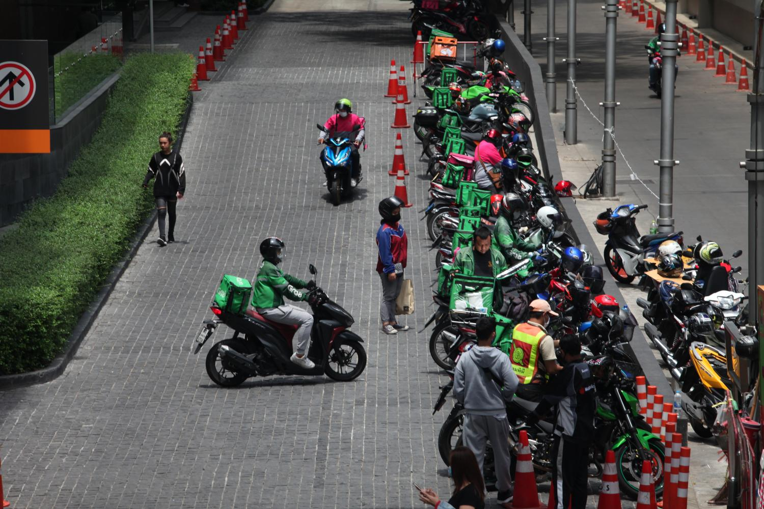 Food delivery bikes of GrabFood, Line Man and Foodpanda line up in front of a mall in the Ratchaprasong-Siam area. (Photo by Apichart Jinakul)