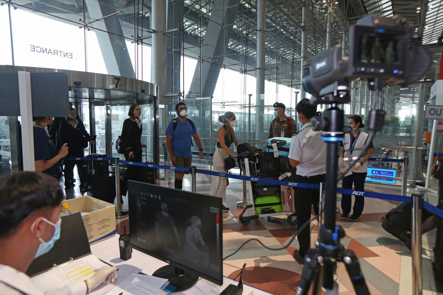 Passengers and crew walk through a health screening with a thermal scanner at Suvarnabhumi airport. International arrivals dropped by 60% during January to May year-on-year. (Photo by Varuth Hirunyatheb)
