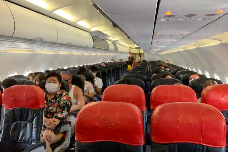 Passengers wear face masks to prevent virus exposure on a Thai AirAsia flight from Phuket to Bangkok.(AFP)