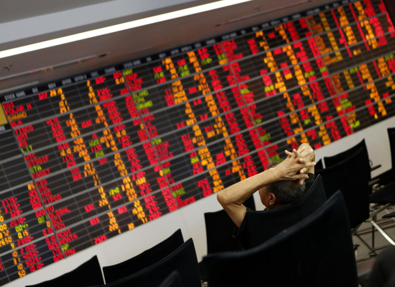 Share prices on an electronic board are mostly in the red as Thai stocks plunge on Monday because of surging infections.  PATTARAPONG CHATPATTARASILL
