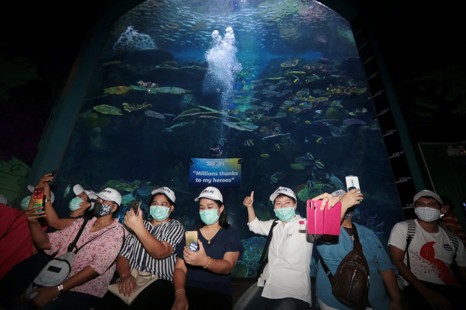 Medics from the Bamrasnaradura Infectious Diseases Institute and their families take a group photo at The SEA LIFE Bangkok. The aquarium invited them for a free visit to show its appreciation for their heroism in fighting the Covid-19 pandemic.  (Photo by Chanat Katanyu)