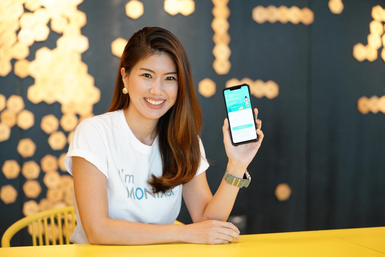 Ms Thiranun holds a mobile phone showing Monix's Hahi Money app.