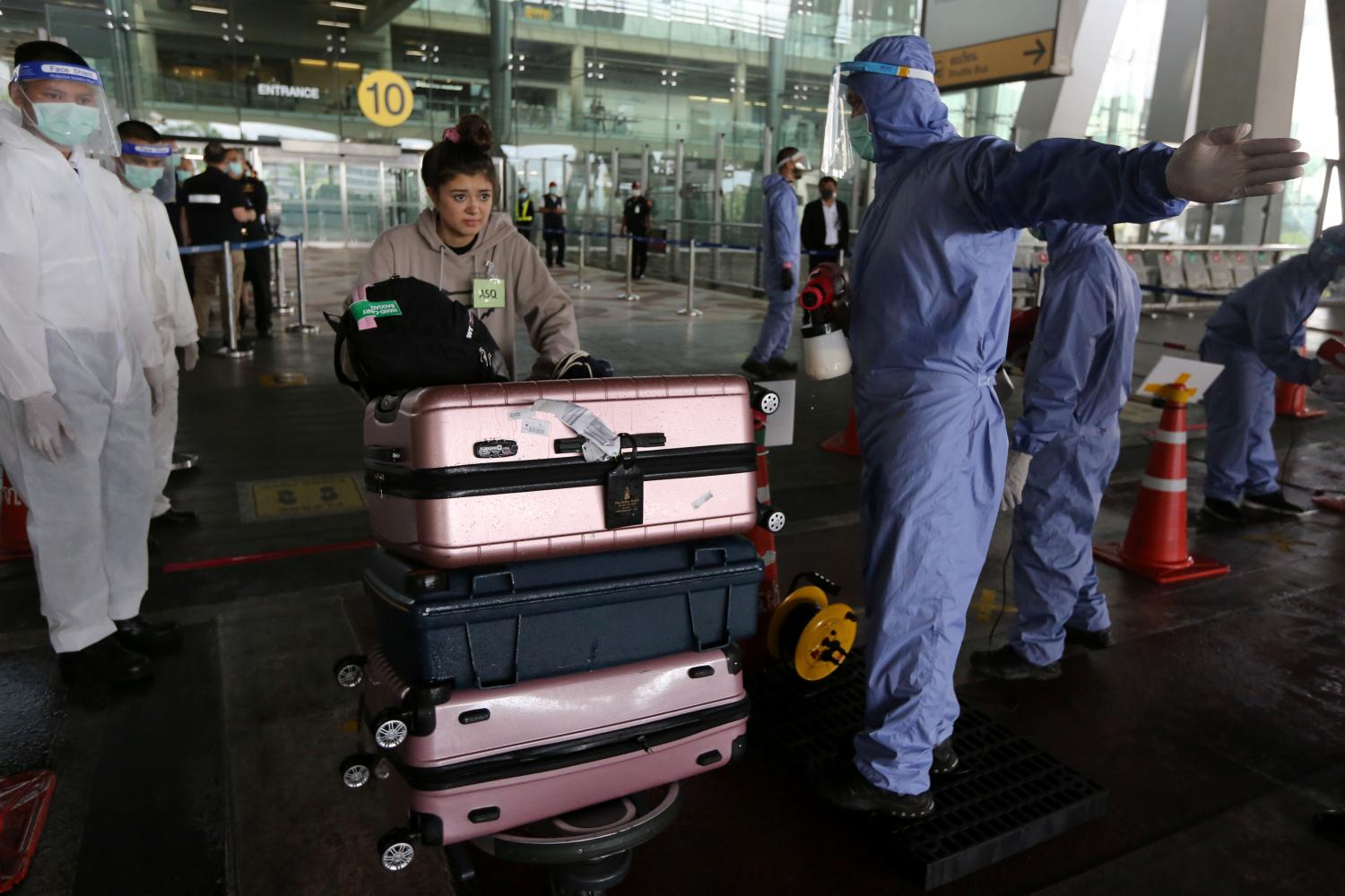 A Thai national arriving at Suvarnabhumi airport yesterday on a Covid-19 repatriation flight pushes a trolley as she is ushered to the right direction by airport staff. A total of 158 Thai people arrived from 13 countries yesterday.Wichan Charoenkiatpakul